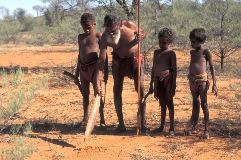 Aboriginal elder teaching youngster to hunt points to animal dropping Central Australia
