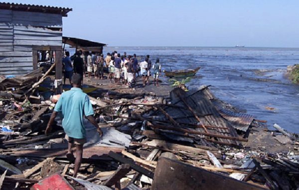 People walk through debris of their houses destroyed in tidal waves on the coastal areas in Colombo, Sri Lanka, Sunday, Dec. 26, 2004. Massive sea waves, apparently triggered by oceanic earthquakes, crashed into coastal villages over a wide area of Sri Lanka on Sunday, killing at least 300 people and displacing 100,000 others. (AP Photo/Eranga Jayawardena)