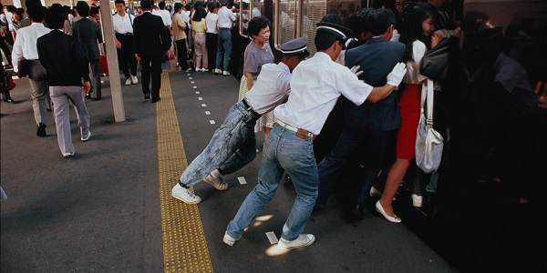 Japan, Honshu, Tokyo, railway staff squeezing commuters onto train